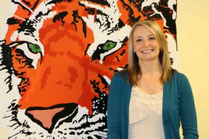 Melissa stands near tiger mural, smiling.