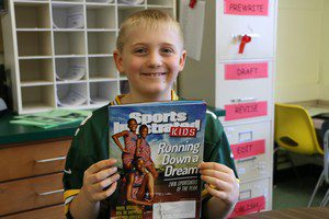 Student holds a copy of Sports Illustrated Kids, smiling.