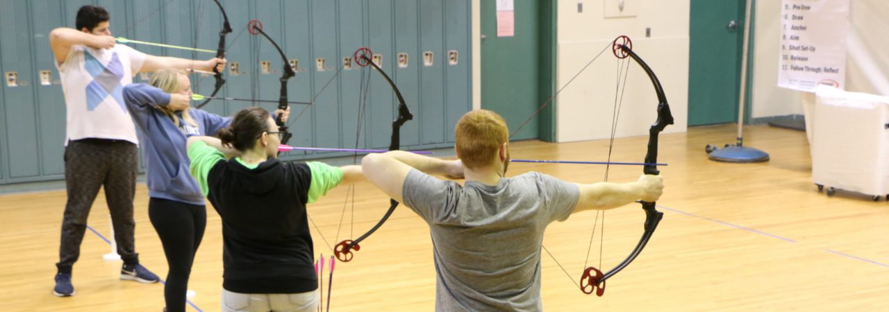 photo of students aiming bows and arrows