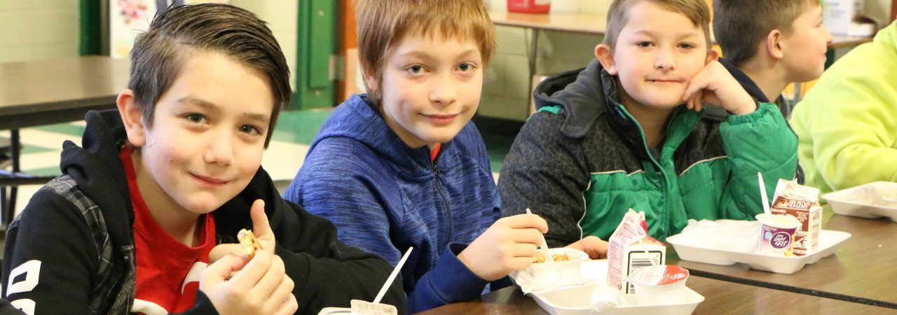 photo of students smiling and eating breakfast