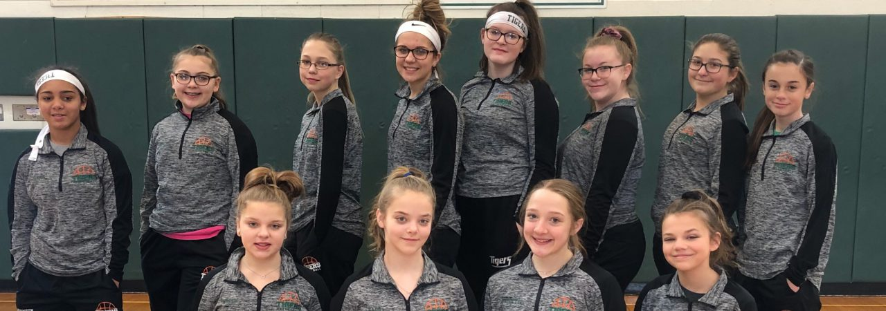 photo shows a group of girls dressed in basketball uniforms smiling
