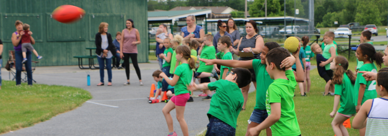 photo shows group of boys and girls throwing football