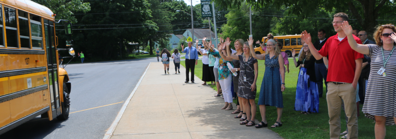 Photo shows teachers waving at bus with kids