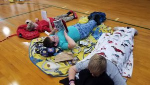 photo shows children laying on gymnasium floor reading books