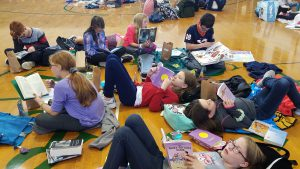 photo shows boys and girls laying and sitting on gymnasium floor reading books