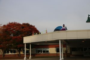 photo shows woman sitting on roof in camp chair