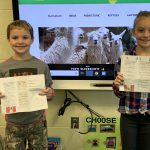 photo shows two kids holding papers up smiling