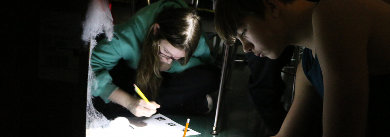photo shows students in darkened room writing