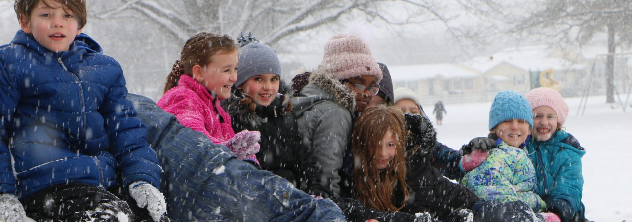 Photo shows students smiling sitting on snow hill