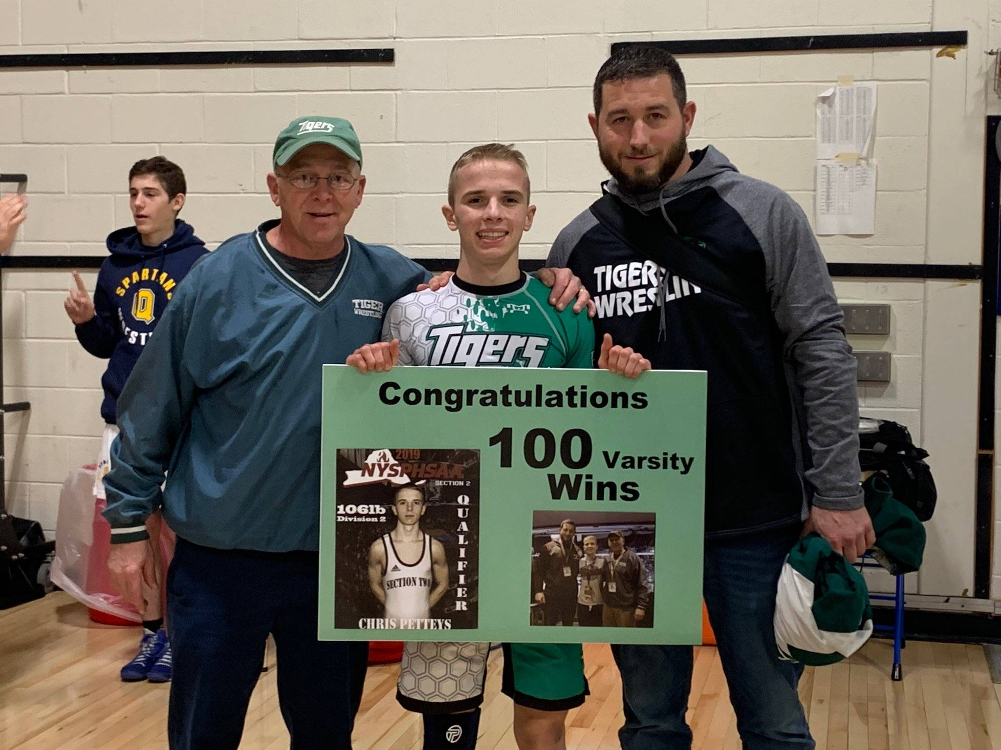 HFHS wrestler Chris holds a poster commemorating his 100th win; he's flanked by his two coaches