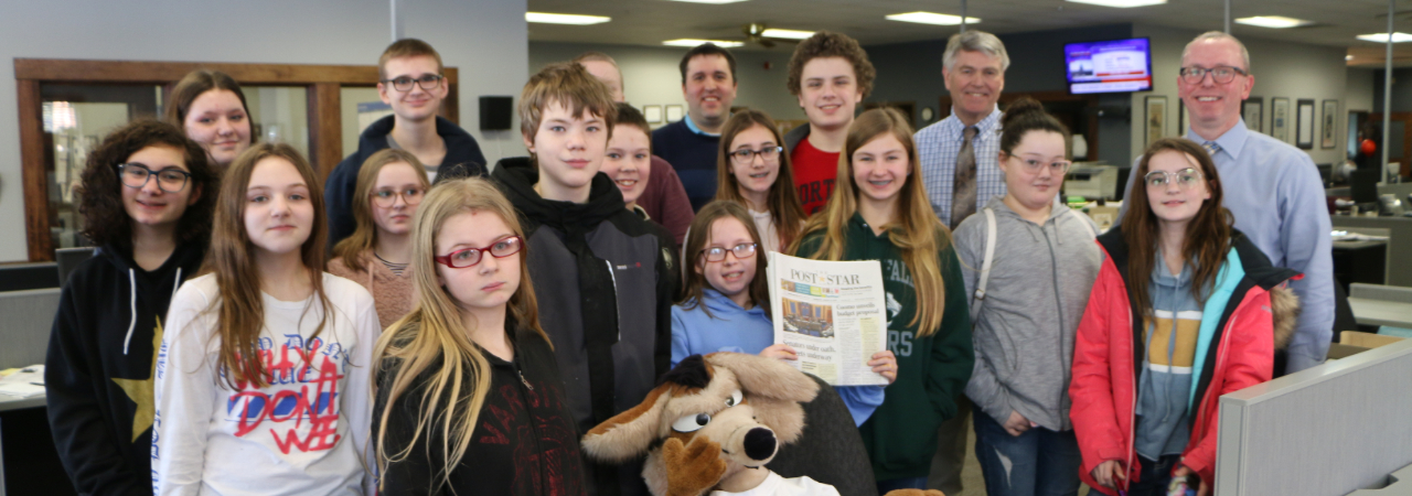 Photo Shows students standing inside post star newsroom smiling