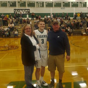 HFHS basketball player Riley Maddison poses for a picture, flanked by his parents, after scoring his 1,000 career point.