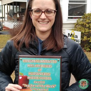 Photo shows woman holding award and smiling