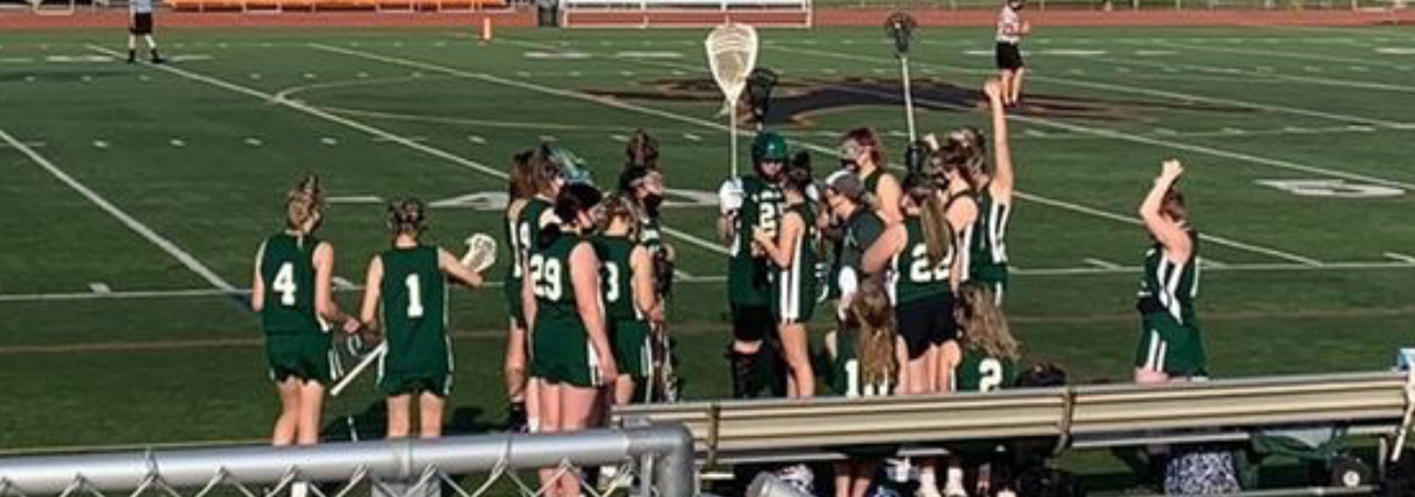 Lacrosse players celebrate on the field
