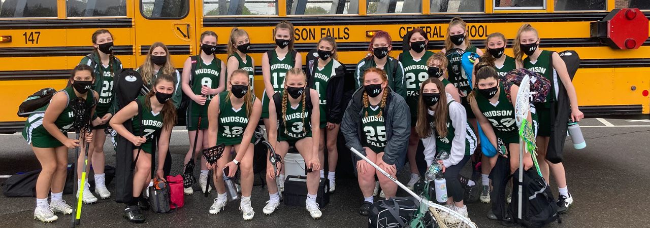 Students wearing uniforms and masks post in front of a school bus